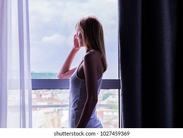 sad lady stay by the window