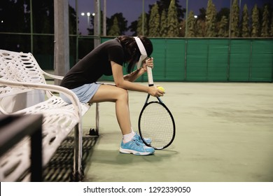 Sad lady tennis player sitting in the court after lose a match - people in sport tennis game concept
