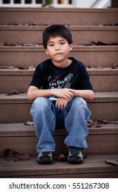 A sad little Asian boy sitting alone on an outdoor, wooden staircase.