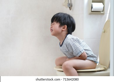 Sad little Asian boy sitting on the toilet suffering from stomach ache.