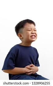 Sad little Asian boy suffering from stomach ache, holding his stomach, isolated on white background.