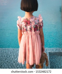 Sad little Asian kid standing by the swimming pool. The depressed Asian kid holding little tedding bear doll with lonely feeling. The lonely little girl need love & care.  Depressed kid concept.