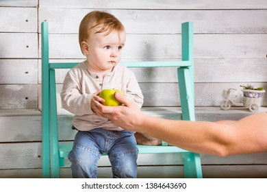 Sad little baby boy take an apple from father. He sits on the steps indoor. White wooden background