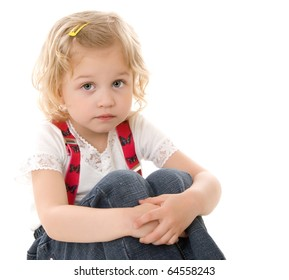 Sad little blond girl in red suspenders sitting on white background