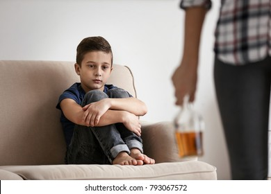 Sad little boy and blurred woman with bottle of alcohol indoors