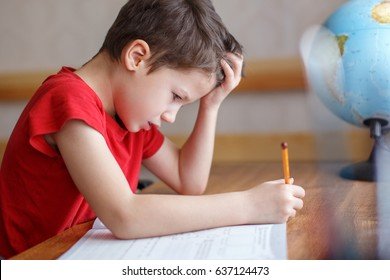 Sad little boy depressed while doing homework