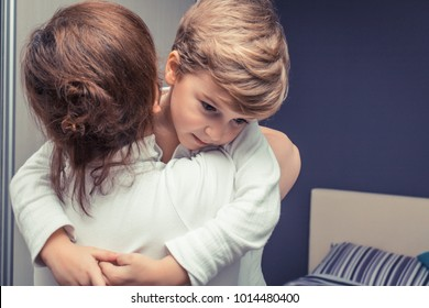 Sad little boy embracing his grandmother in the bedroom.