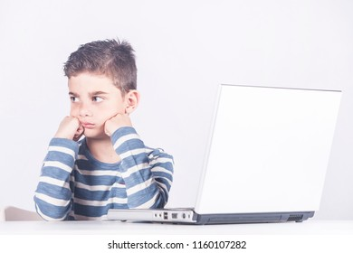 Sad little boy in front of a computer. Cyber bullying concept
