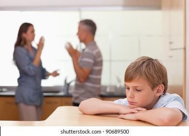 Sad little boy hearing his parents having am argument in a kitchen