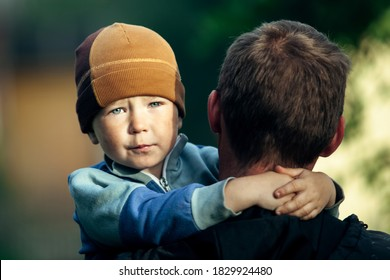 Sad little boy in his father's arms.