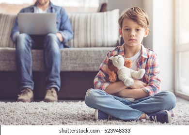 Sad little boy is holding a toy and looking at camera while his father is working in the background