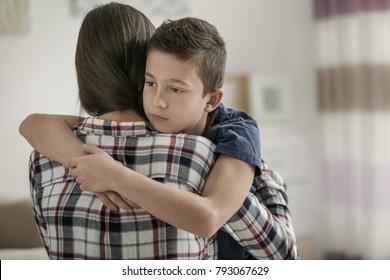 Sad little boy hugging his mother at home