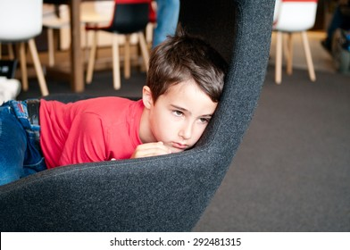 Sad little boy left alone in chair