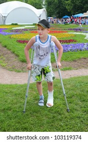 Sad little boy on crutches in beautiful summer park; leg in cast