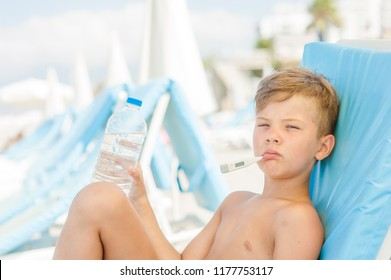 Sad little boy on hot beach with sunstroke measures the temperature and holds a bottle of water
