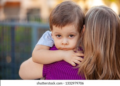 sad little boy on mother's shoulder