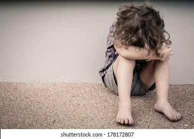 sad little boy sitting near the wall