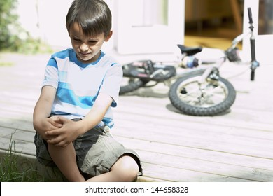 Sad little boy sitting on porch of house with bicycle in background