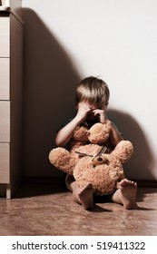 Sad little boy sitting on the floor with bear toy, covering his face and crying. Child abuse.