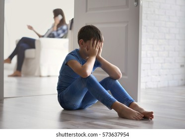 Sad little boy sitting on floor beside door