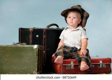 Sad little boy sitting on an old suitcase. He is wearing a hat