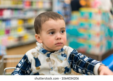 Sad little boy in the store. Sad baby in the supermarket