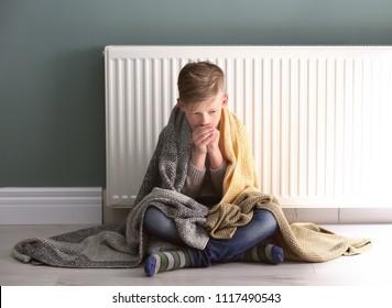 Sad little boy suffering from cold on floor near radiator