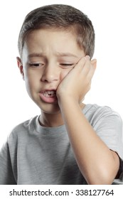 sad little boy suffering from toothache pain in mouth, holding his cheek, dental pain