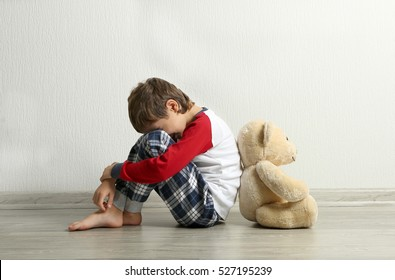 Trauriger kleiner Junge mit Teddybär auf dem Boden im leeren Raum