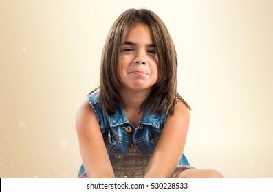 Sad little brunette girl on ocher background