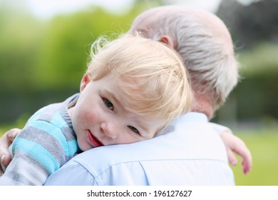 Sad little child, adorable blonde toddler girl, relaxing and comforting on the shoulder of her grandparents