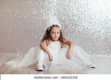 sad little child girl in blue dress sitting on the floor with confetti on background with silver bokeh. after birtday party