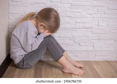 Sad little child girl sitting on floor in corner at home.