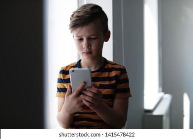 Sad little child with smartphone indoors. Danger of internet