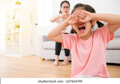 the sad little children girl sitting on the wooden floor crying loudly when the mother pointing to her sitting on sofa in the living room angry curse on the morning of the holiday.