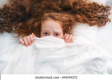 Sad little girl afraid sleeping and pulling quilt on head.
