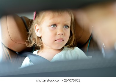 sad little girl in the car seat