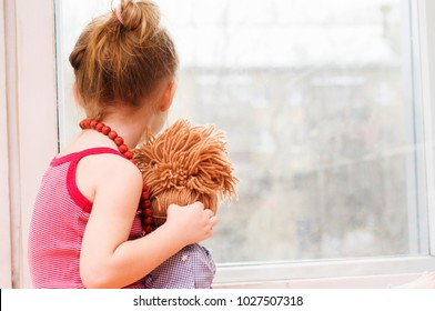 Sad little girl with a doll waiting for her mother near the window
