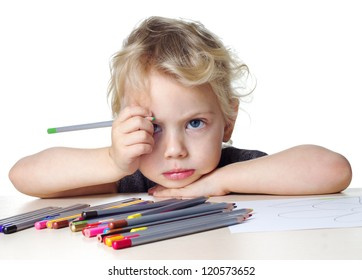 sad little girl draws with colored pencils