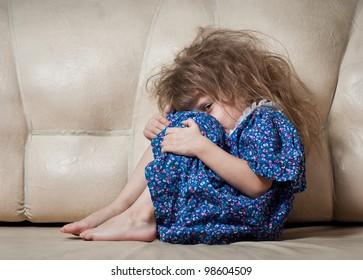 Sad little girl hides her face