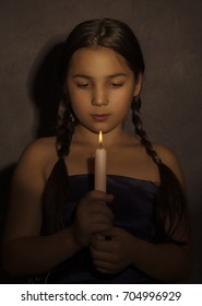 sad little girl holding candle in dark room