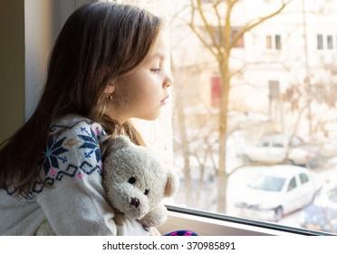 Sad little girl holds a teddy bear looks out the window.