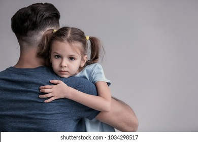 Sad little girl hugging her father on grey background