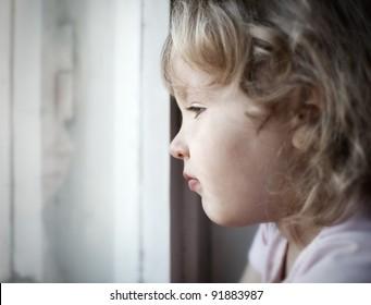 Sad little girl looking at window