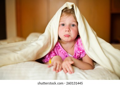 Sad little girl lying on bed under blanket and posing in room of her flat