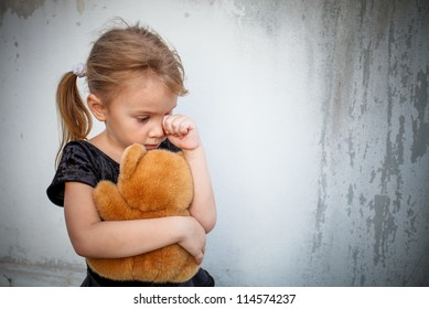 sad little girl on background the wall with toy