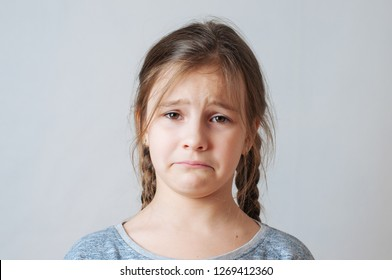 Sad little girl with pigtails portrait on a neutral grey background