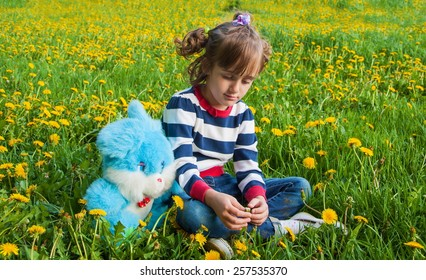 Sad little girl with plush rabbit on the lawn