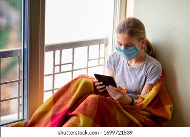 Sad little girl in protective mask sitting on the window with e-book or tablet reading and studying at home isolated. Coronavirus quarantine distance education concept.