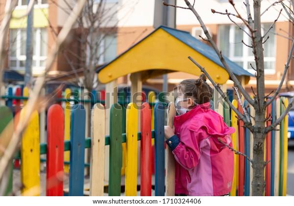 Niña triste con una máscara protectora en el fondo del patio cerrado al aire libre. Un niño con una máscara médica camina por el parque. Medidas de cuarentena contra COVID-19. Pandemia de coronavirus.